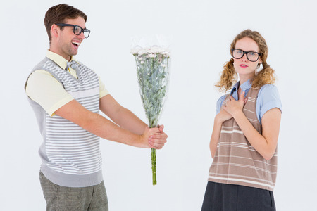 woman white background: Geeky hipster offering flowers to his girlfriend on white background