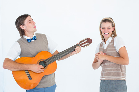 serenading: Geeky hipster serenading his girlfriend with guitar on white background