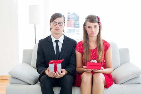 together with long tie: Pareja geek Sin sonre�r con el regalo en el sof� Foto de archivo