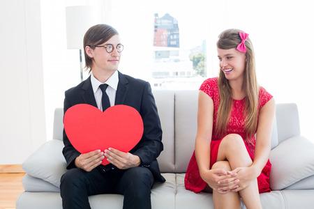 together with long tie: Pareja geek lindo con forma de coraz�n rojo en el sof�
