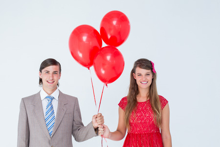 Smiling geeky couple holding red balloons on white background photo