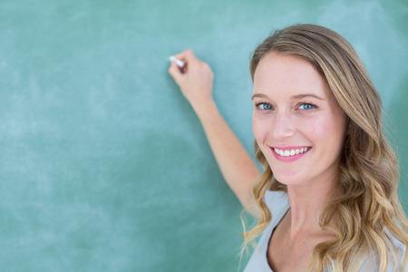 笑顔の先生の教室で黒板に書く