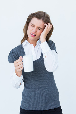 wincing: Woman with headache holding mug on white background