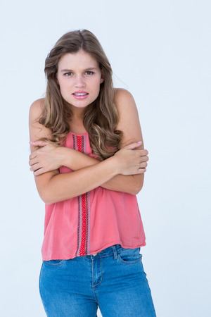 shivering: Shivering woman holding her arms on white background