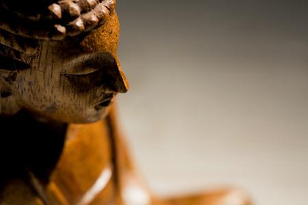 wood figurine: Buddha statue on a table shot in studio Stock Photo