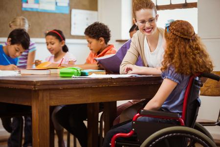 persona en silla de ruedas: Maestro ayudar a un alumno discapacitado en la escuela primaria Foto de archivo