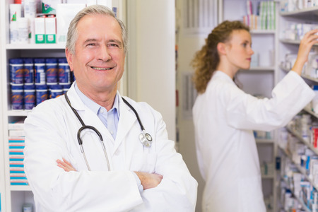 Pharmacist looking at camera with student behind him in the pharmacy photo