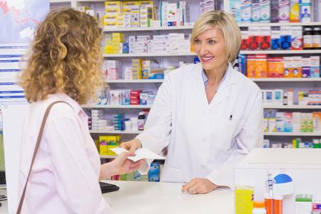 pharmacist: Customer handing a prescription to a smiling pharmacist in the pharmacy