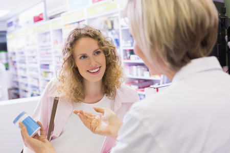 pharmacist: Pharmacist and her customer talking about medication in the pharmacy Stock Photo