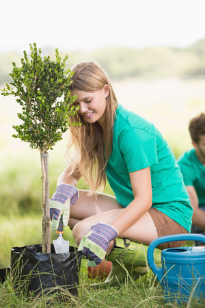 young tree: Pretty blonde gardening for her community on a sunny day Stock Photo