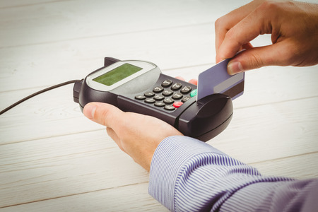 eftpos: Man swiping his credit card on a wooden table Stock Photo