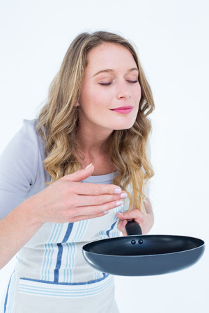 smelling: Smiling woman smelling the meal on white background