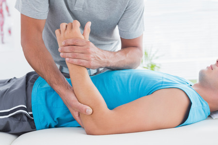 elbow pain: Doctor examining his patient arm in medical office Stock Photo