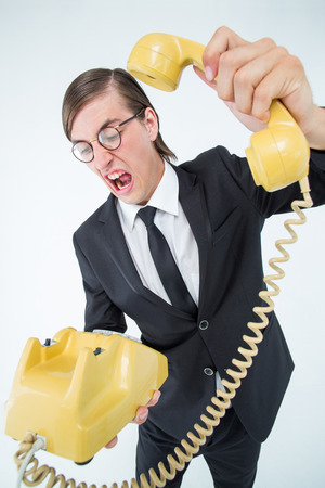 hanging up: Geeky businessman shouting and hanging up the telephone on white background