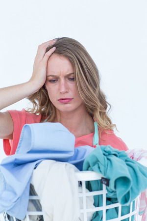 dirty clothes: Woman looking at dirty clothes on white background Stock Photo