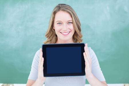 Smiling teacher holding tablet pc in front of blackboard in classroom photo
