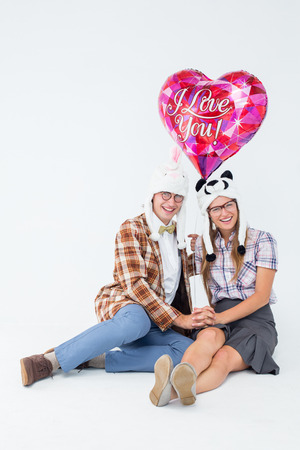Geeky hipster in love couple looking at camera on white background photo