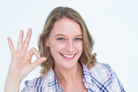 okay: Pretty hipster doing okay sign on white background