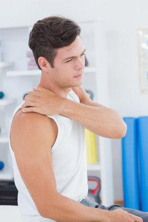 douleur epaule: Jeune homme souffrant de douleur � l'�paule dans le cabinet m�dical