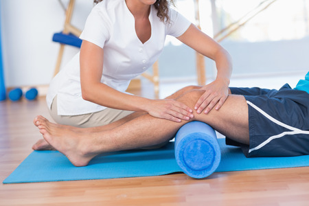 Trainer working with man on exercise mat in fitness studio Stock Photo
