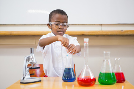 science scientific: Cute pupil looking at liquids at elementary school