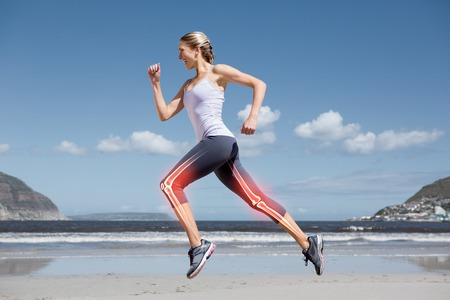 bone health: Digital composite of Highlighted leg bones of jogging woman on beach