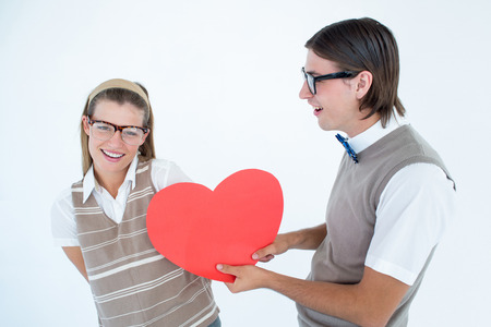 Geeky hipster offering red heart to his girlfriend on white background photo