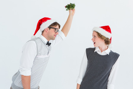 geeky: Geeky hipster holding mistletoe on white background