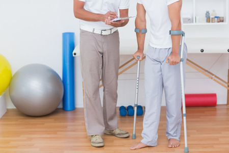 naprapathy: Doctor showing clipboard to his patient with crutch in medical office