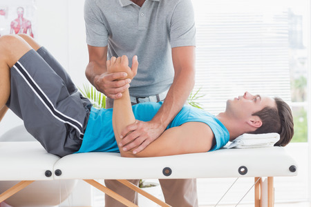 massage: Doctor examining his patient arm in medical office Stock Photo