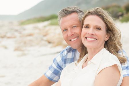parejas felices: Casual pareja sonriendo a la c�mara en la playa Foto de archivo