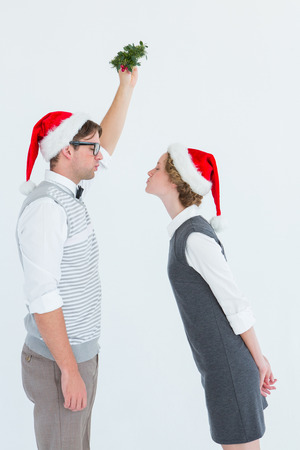 Geeky hipster kissing under mistletoe on white background