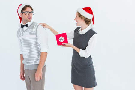 Geeky hipster offering present to her boyfriend on white background photo