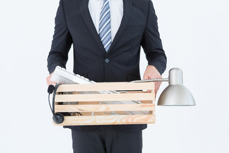 unemployed dismissed: Businessman holding box of his things on white background