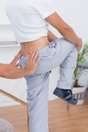 coccyx: Doctor examining his patient back in medical office Stock Photo