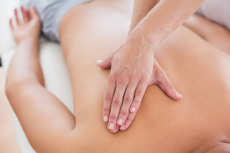 male massage: Physiotherapist doing back massage to her patient in medical office Stock Photo