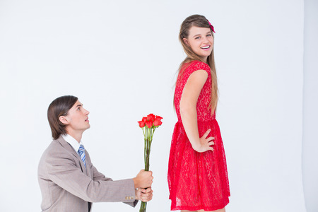 together with long tie: Hipster on bended knees behind his girlfriend on white background