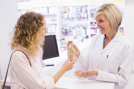 drugstore: Farmacéutico que da la medicina al cliente en la farmacia