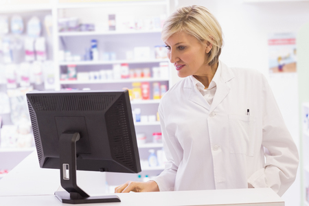 Pharmacist using the computer at pharmacy