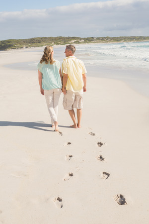 escapism: Happy couple walking holding hands at the beach Stock Photo