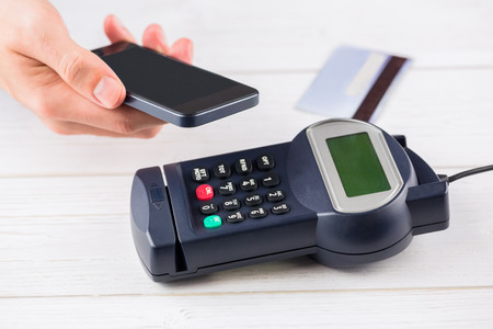 eftpos: oMan using smartphone to express pay on a wooden table Stock Photo