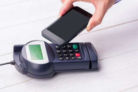 eftpos: Man using smartphone to express pay on a wooden table