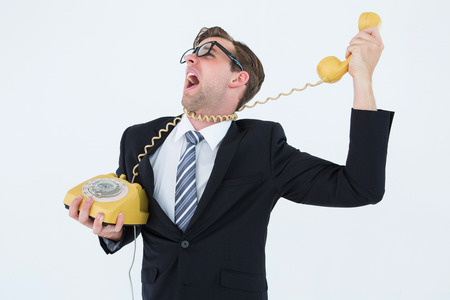 strangling: Geeky businessman being strangled by phone cord on white background Stock Photo
