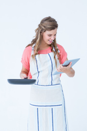 Happy hipster woman holding laptop and frying pan on white background photo