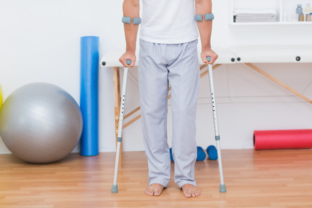 physical: Patient standing with crutch in medical office Stock Photo