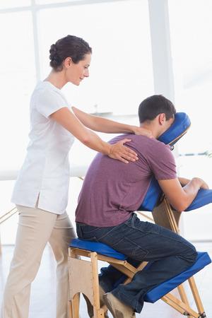 massage chair: Man having back massage in medical office