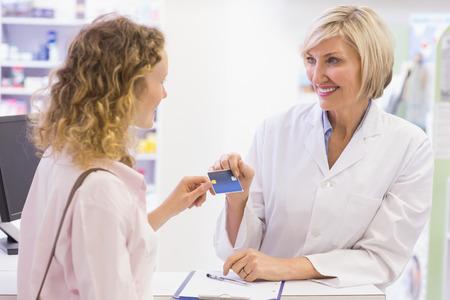 costumer: Pharmacist giving credit card to costumer at pharmacy Stock Photo