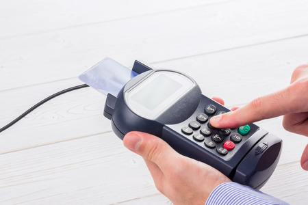 consumerism: Man entering his pin on terminal on a wooden table Stock Photo