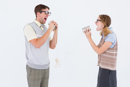 tin can phone: Geeky hipster couple speaking with tin can phone on white background