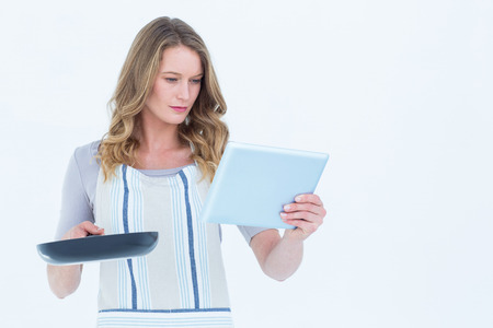 Concentrated woman holding frying pan and tablet pc on white background photo